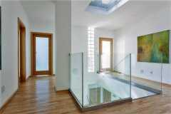 Stairs, glass banister and doors in modern hallway